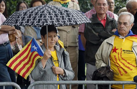 "A woman holds an ""Estelada"" (Catalonia separatist flag) flag as she attends a ceremony to mark the ""Diada de Catalunya"" (Catalunya's Nationa"