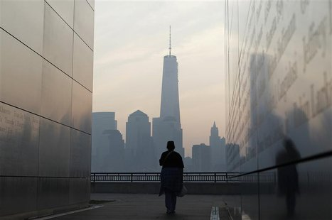 A woman looks out at New York's Lower Manhattan and One World Trade Center from inside the 9/11 Empty Sky memorial at Liberty State Park in