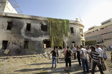 People look at the site of an explosion at a Libyan Foreign Ministry building in Benghazi September 11, 2013. REUTERS/Esam Omran Al-Fetori
