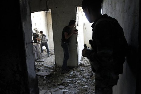 A Free Syrian Army fighter (L) moves through a hole in a wall as his fellow fighter watches while an activist (C) is seen filming inside a h