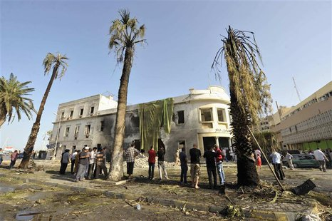 People stand near a Libyan Foreign Ministry building in Benghazi after an explosion in Benghazi September 11, 2013. REUTERS/Esam Omran Al-Fe
