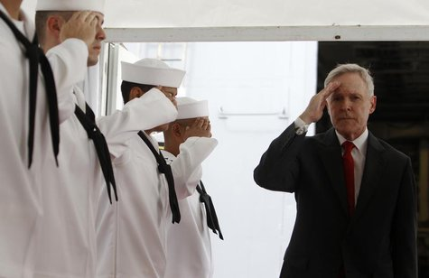 U.S. Secretary of the Navy Ray Mabus salutes servicemen onboard the USS Freedom littoral combat ship during a visit at Changi Naval Base in