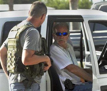 Pastor Terry Jones, (R), talks to a member of the Polk County Sheriff's Department as he sits in his vehicle prior to his arrest after being