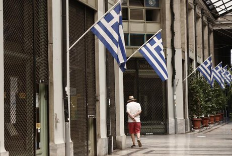 A man walks by a row of closed shops at an arcade in central Athens August 26, 2013. REUTERS/John Kolesidis
