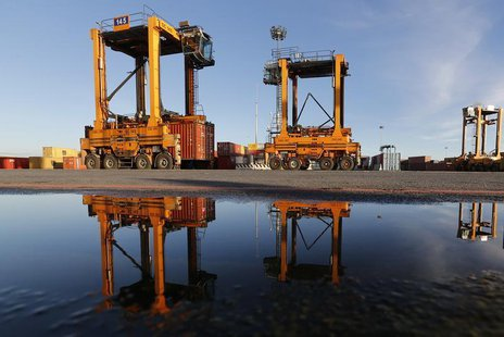 Container cranes are seen reflected in water at Italy's biggest port Gioia Tauro in the southern Italian region of Calabria, November 8, 201