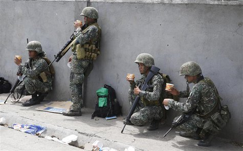 Members of Philippine Marines eat a meal at their positions on the fourth day of a government stand-off with the Moro National Liberation Fr