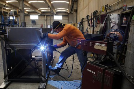 A worker welds a metal furnace in a factory in Gravellona Lomellina, 45km (27 miles) southwest of Milan, June 11, 2013. REUTERS/Stefano Rell