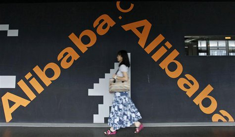 An employee walks past a wall painted with the logo of Alibaba (China) Technology Co. Ltd at its headquarters office on the outskirts of Han