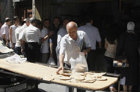 Syrians wait in line to buy bread at al-Shaalan market in Damascus August 28, 2013. REUTERS/ Khaled al-Hariri