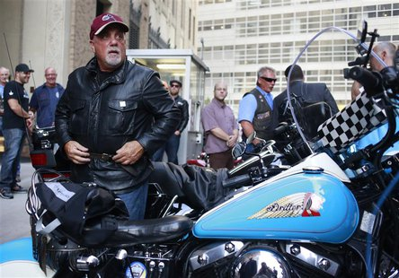 Singer Billy Joel gets off a motorcycle after riding from the Rescue 1 firehouse on West 43rd Street downtown to Ground Zero to honor the vi