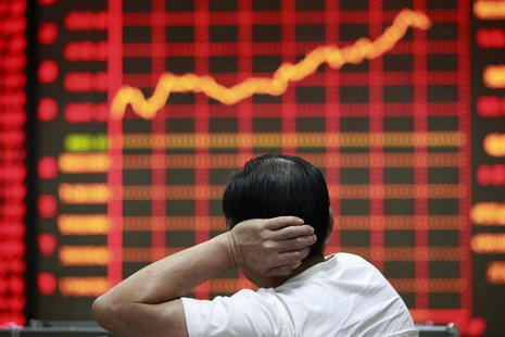 An investor looks at an electronic board showing stock information at a brokerage house in Huaibei, Anhui province September 9, 2013. REUTER