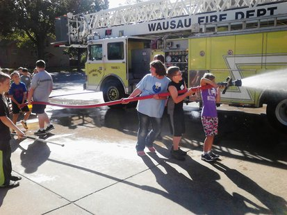 Students from Wausau Montessori spray down a fire truck at the Wausau Fire Department, September 11 2013