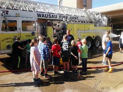 Wausau Montessori students get a lesson in fire truck cleaning at Wausau Fire Department, September 11 2013