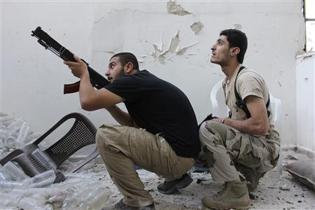A Free Syrian Army fighter points his weapon as his fellow fighter watches in Aleppo's Al-Ezaa neighbourhood September 11, 2013.  REUTERS/Aref Hretani
