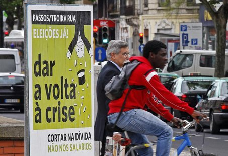 "People pass by a political poster reading, ""Passos/Toika out. Elections now. Turn the crisis around. Cut the debt and not the salaries"", on"