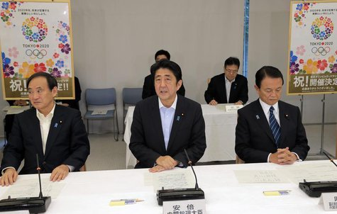 Japan's Prime Minister Shinzo Abe (C), flanked by Chief Cabinet Secretary Yoshihide Suga (L) and Finance Minister Taro Aso, speaks about Tok