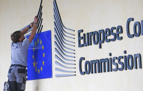 A worker adjusts and cleans the logo of the European Commission at the entrance of the Berlaymont building, the EC headquarters, in Brussels