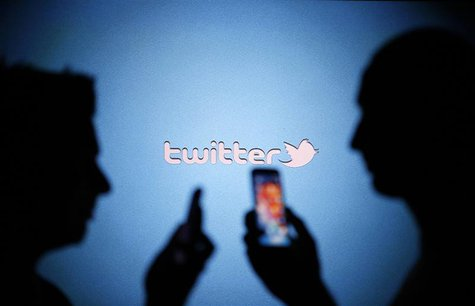 Men are silhouetted against a video screen with a Twitter logo as they pose with Samsung S3 and S4 smartphones in this photo illustration ta
