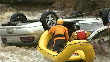 Emergency personnel work to rescue a man trapped in his vehicle during a flooding of Rock Creek in Lafayette, Colorado September 12, 2013, in this photo courtesy of CBS4 Denver.  REUTERS/CBS4 Denver/Handout via Reuters