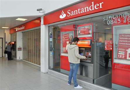 Customers use ATM machines at the Surrey Quays branch of Santander Bank, whilst the premises remain closed , in Surrey Quays, south London,