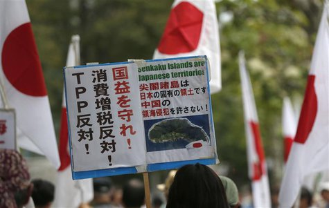"A member of the nationalist movement ""Ganbare Nippon"" holding a placard of disputed islands known as Senkaku in Japan and Diaoyu in China, w"