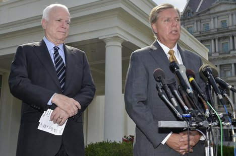 U.S. Senator Lindsey Graham (R-SC), (R), makes remarks to the media as U.S. Senator John McCain (R-AZ), (L), listens, after meeting with U.S
