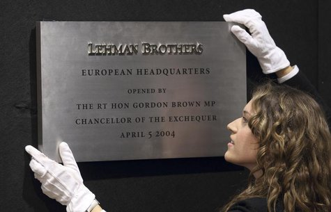 A Christie's employee poses for a photograph with the plaque from Lehman Brothers' European headquarters at Christie's in central London, Se