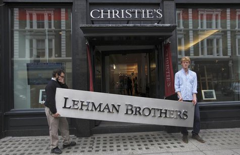 Christie's employees pose for a photograph with a Lehman Brothers sign at Christie's in central London September 24, 2010. REUTERS/Andrew Wi