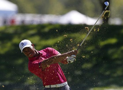 Tiger Woods of the U.S. watches his approach shot on the first hole during the third round of the BMW Championship golf tournament at the Co