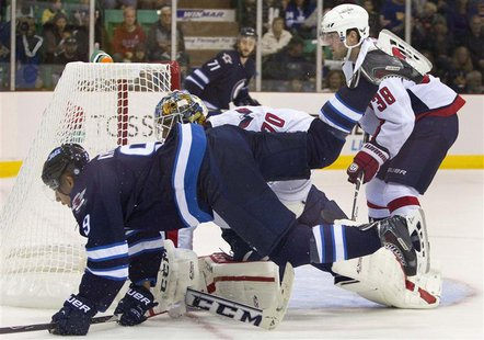 Winnipeg Jets Evander Kane (L) is tripped up by Washington Capitals goalie Branden Holtby in the first period of their NHL pre-season hockey