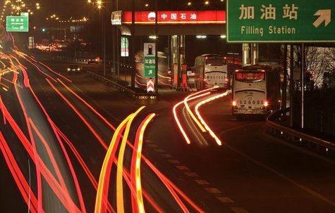 Cars drive into a Petrol China gas station, as other vehicles drive past on the Beijing-Tibet expressway in Beijing, March 23, 2012. CREUTER
