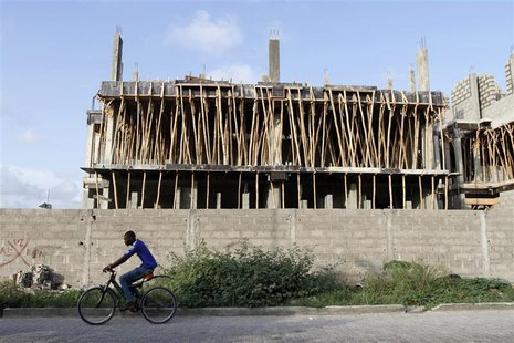 A man rides a bicycle past a building under construction in the Victoria Island district in Nigeria's commercial capital Lagos September 6,