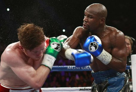 WBC/WBA 154-pound champion Canelo Alvarez (L) takes a punch from Floyd Mayweather Jr. of the U.S. at the MGM Grand Garden Arena in Las Vegas