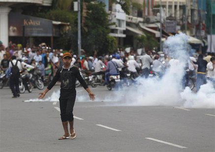 A protester supporting the opposition Cambodia National Rescue Party (CNRP) reacts as police fire tear gas during clashes near the Royal Pal