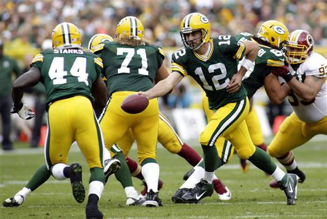 Green Bay Packers quarterback Aaron Rodgers (C) hands off the ball to running back James Starks (L) during the first half of their NFL footb