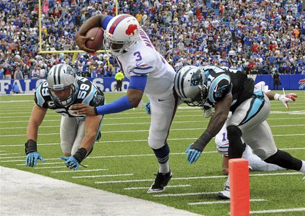 Buffalo Bills quarterback EJ Manuel (C) is knocked out of bounds by Carolina Panthers cornerback Captain Munnerlyn (R) and linebacker Luke K
