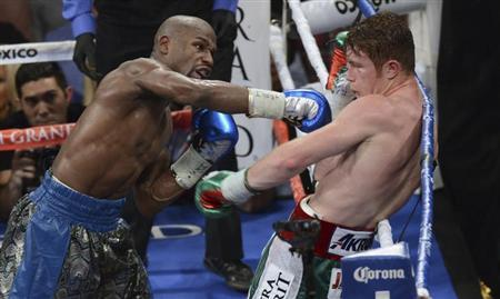 Floyd Mayweather Jr. (L) of the U.S. punches on WBC/WBA 154-pound champion Canelo Alvarez of Mexico during their title fight at the MGM Grand Garden Arena in Las Vegas, Nevada, September 14, 2013. Credit: REUTERS/Mark Hundley