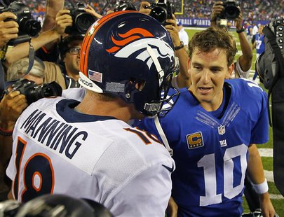 Denver Broncos quarterback Peyton Manning (L) talks with his brother, New York Giants quarterback Eli Manning after the Broncos defeated the