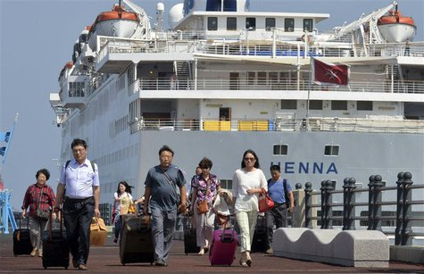Passengers leave Chinese cruise ship Henna, which is stranded at the port of Jeju on Jeju island, south of Seoul September 15, 2013, to go t