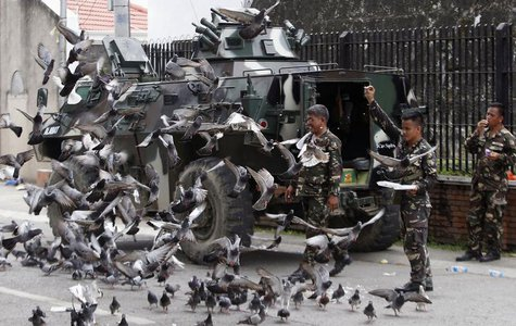 Government soldiers of Task Force Zamboanga feed pigeons with bread crumbs near a military command post during a lull in fighting with Musli