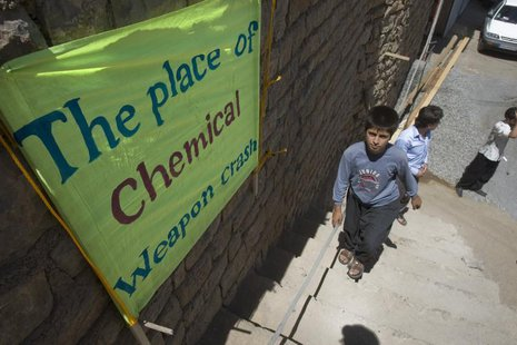 A boy walks past a placard which shows the place of an Iraqi chemical attack during the 1980-1988 war against Iran, in Nowdesheh in Kermansh