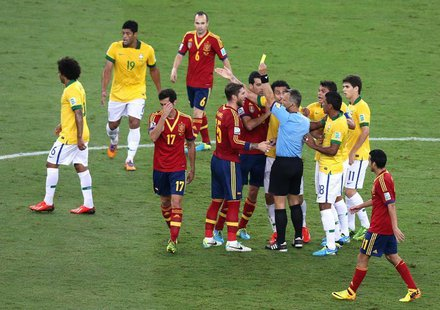 Spain's Alvaro Arbeloa (3rd L) is issued a yellow card as teammate Sergio Ramos (C) argues with the referee against Brazil during the Confed