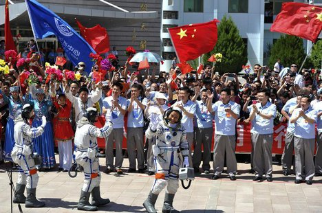 Chinese astronauts (from L to R) Wang Yaping, Zhang Xiaoguang and Nie Haisheng wave before leaving for the Shenzhou-10 manned spacecraft mis