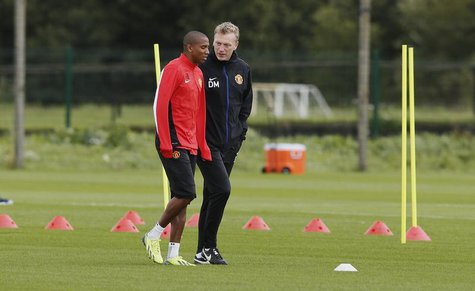 Manchester United's manager David Moyes (R) talks with player Ashley Young during a soccer training session at the club's Carrington trainin