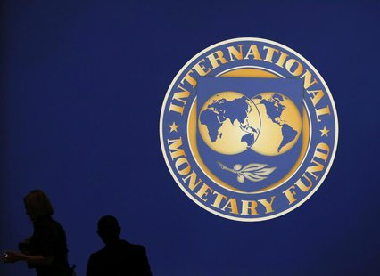 Visitors are silhouetted against the logo of the International Monetary Fund at the main venue for the IMF and World Bank annual meeting in