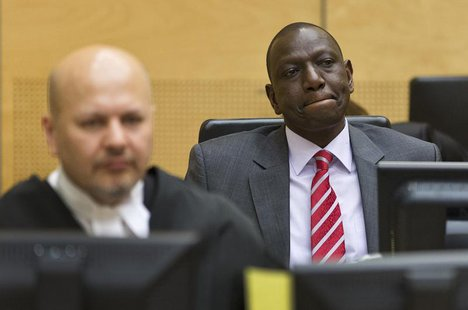 Kenya's Deputy President William Ruto (R) reacts as he sits in the courtroom before his trial at the International Criminal Court (ICC) in T