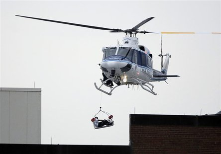 A helicopter pulls up an apparent shooting victim as it hovers over a rooftop on the Washington Navy Yard campus in Washington, September 16