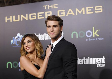 "Cast member Liam Hemsworth poses with actress Miley Cyrus at the premiere of ""The Hunger Games"" at Nokia theatre in Los Angeles, California"