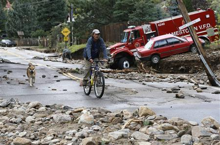 A resident rides down Main Street with his dog in Jamestown, Colorado, after a flash flood destroyed much of the town, September 14, 2013.  REUTERS/Rick Wilking