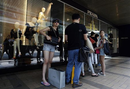 Mainland Chinese customers line up outside a Prada store at Hong Kong's shopping Tsim Sha Tsui district September 16, 2013, one day before t
